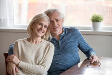Family portrait of happy senior couple sit at home table hugging, loving aged husband and wife embrace posing for picture, smiling elderly man hold beloved woman in arms looking at camera.