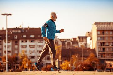 Full of energy,senior man running in city