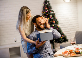 Young man getting present from loving woman for Christmas or New Year Eve
