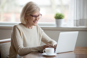 Happy aged woman in glasses working at laptop drinking tea, smiling senior female using computer browsing or surfing internet, reading news online, excited elderly lady texting message at pc at home