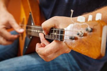 man playing the balalaika. hands closeup
