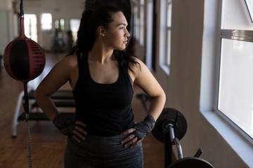 Female boxer looking through window in fitness studio