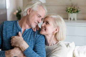 Portrait of happy sensual senior couple looking in eyes holding hands posing for family picture, smiling romantic aged husband and wife hugging expressing love and support shooting at home together