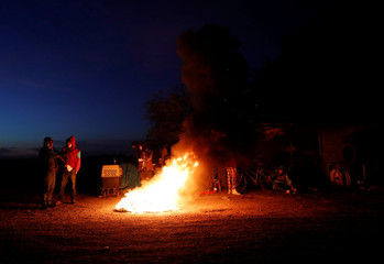 Migrants, part of a caravan of thousands traveling from Central America en route to the United States, warm themselves over a bonfire at a makeshift camp at a gas station where the migrants wait for buses in Navojoa