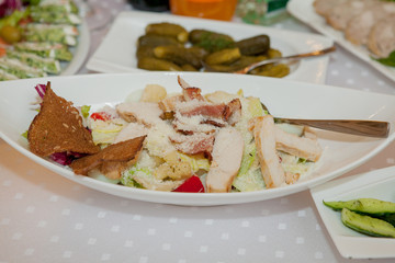 Plate with chicken salad on table. Catering service. Restaurant table with food. Huge amount of food on the table. Plates of food