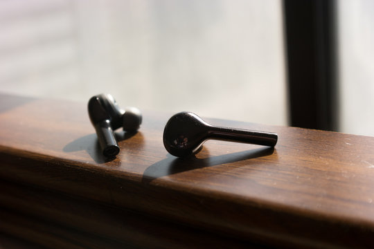 wireless black earbuds on a wooden texture