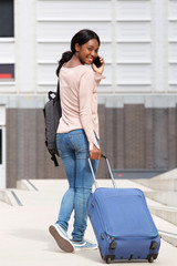 behind of happy young african american woman walking with suitcase bag and cellphone