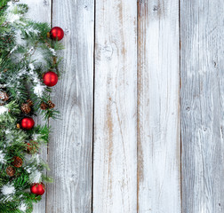 Christmas background with snowy evergreen branches and red ornaments on aged white wood