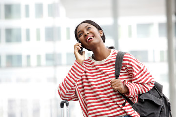 cheerful young african american woman waiting at airport with mobile phone and bags