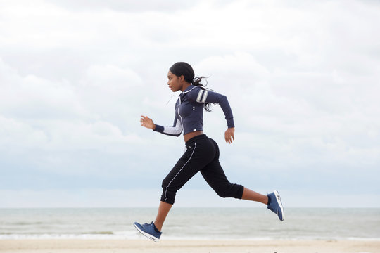 side portrait of african american woman running by the beach