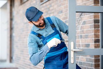Builder in uniform installing a door lock into the entrance door of a new house outdoors