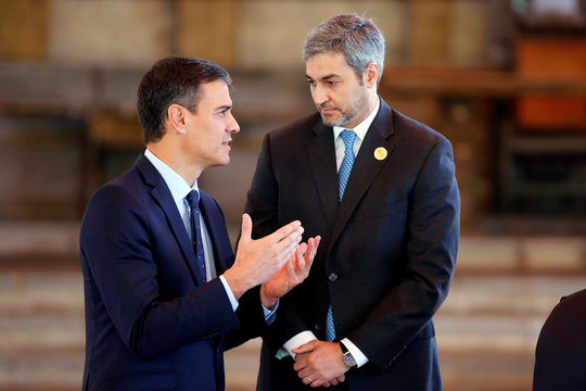 Spain's Prime Minister Pedro Sanchez speaks with Paraguay's President Mario Abdo Benitez before a group photo during the XXVI Ibero-American Summit in Antigua Guatemala