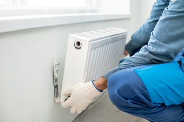 Workman mounting water heating radiator on the white wall indoors, close-up view Wall mural