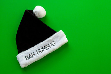 black and white fur pompom hat with the words Bah Humbug on the brim isolated on a green background with copy space