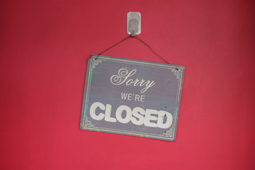 "Aged fancy writing ""Sorry we are closed "" sign hanging crooked on a flat red wall.  Some stains on both wall and sign"