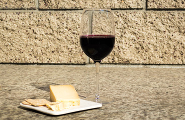 glass of red wine with cheese and crackers on a small plate outdoors near a stone wall