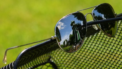 Sunglasses with garden reflections on a steel seat