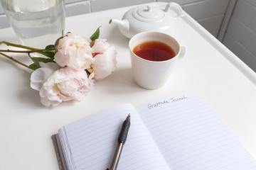 Closeup of gratitude journal on white table with peonies, cup of tea and teapot (selective focus)