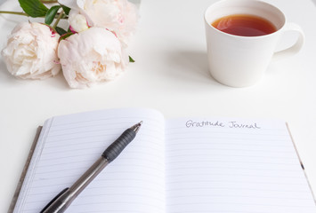 Closeup of gratitude journal on white table with pen, peonies and cup of tea (selective focus)