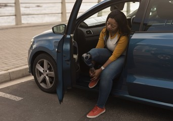 Disabled woman tying shoelace while sitting in car