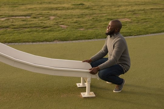 Man sitting near ladder slide