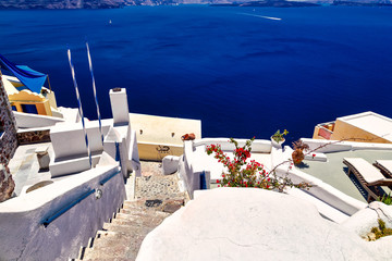 steps down to the hotels and the sea white architecture on the famous island of Santorini, sun beds and a terrace on the sides