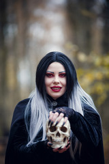 Photo of witch girl in black cloak with skull