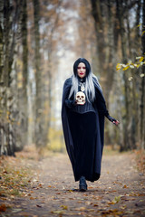 Portrait of witch girl in full growth in black cloak with skull