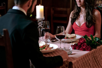 Attractive couple in love is dating and drinking wine during romantic dinner in the restaurant.