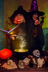 Picture of smiling witches in black hats with book and magic cauldron at table with pumpkin and skulls