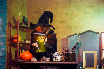 Portrait of blonde witch in black hat reading spell over pot with green steam