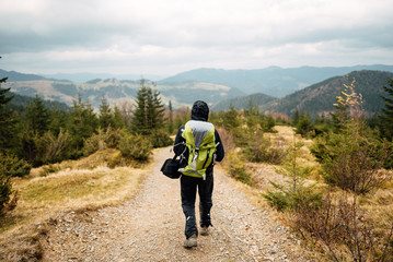 Man with a backpack walking along the road. There are mountains on the horizon. The sky is blue and cloudy.