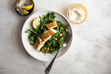 Fried halibut fist with spiced chickpeas and hen salad served on plate