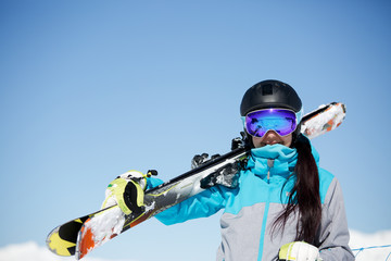 Photo of sport woman with skis on shoulder