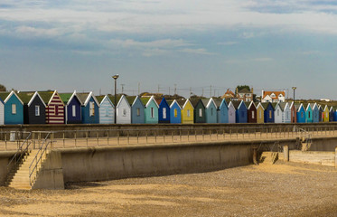 Landscape of colourfully painted generic beach huts along a promenade, with steps down to an empty beach. Blue sky with white clouds.