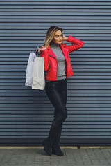 Young beautiful blonde girl with purchases, packages after shopping