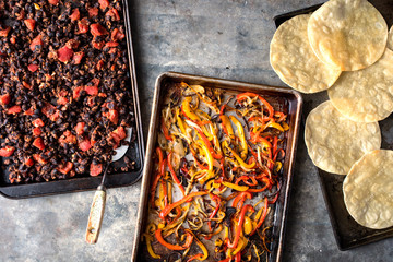 Close up of tostadas, bell pepper and black beans on baking tray