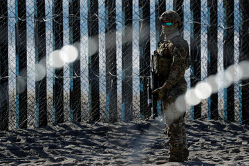 An armed U.S. Customs and Border Patrol agent stands watch at the border fence next to the beach in Tijuana, at the Border State Park in San Diego, California