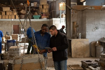Workers discussing in foundry workshop