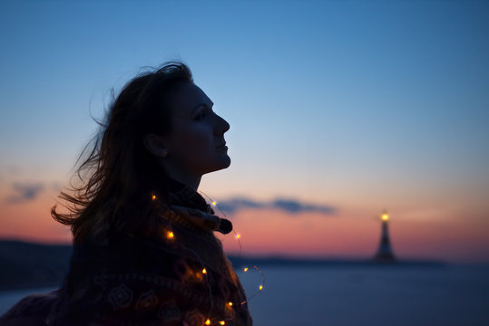young woman looking at sea and lighthouse after sunset
