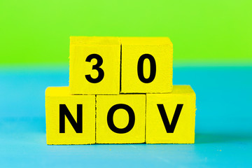 NOV 30, yellow cube calendar on blue wooden surface with copy space