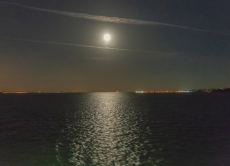 Moon And Reflection Over The Sea Surface