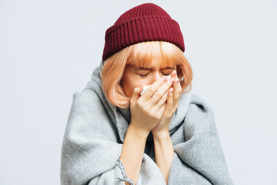 Unhealthy young woman in red hat, warm scarf with paper napkin sneezing, experiences allergy symptoms, caught a cold, closed eyes. Sick desperate woman has flu. Sinusitis, cold, sneezing concept