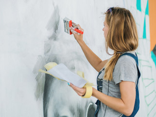 Beautiful Young Blonde Girl making graffiti of big eye with aerosol spray on urban street wall. Creative art. Talented student in denim overalls drawing picture