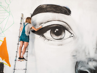 Beautiful girl making graffiti of big female face with aerosol spray on urban street wall. Creative art. Talented student in denim overalls drawing picture