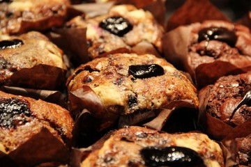 Chocolate chip and blueberry muffins with dark marmalade topping or filling. Warm homemade muffins or cupcakes at a bakery around Christmas. Sweet, delicious and tasty dessert for tea time in winter