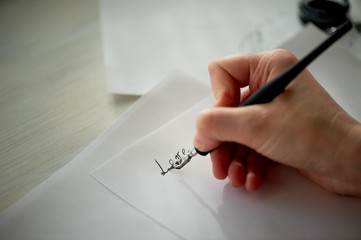 A woman's hand writes with ink, a fountain pen. Writing. The creative process of creating a work