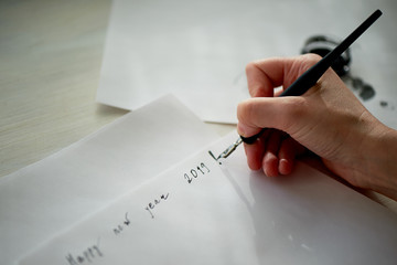 A woman's hand writes with ink, a fountain pen. Writing. The creative process of creating a work. Phrase new year 2019. Wish list and plans