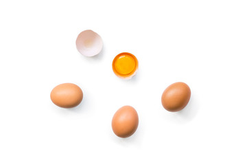 fresh brown organic chicken eggs broken with yolk and egg white isolated on white background. Vertical composition. Top view