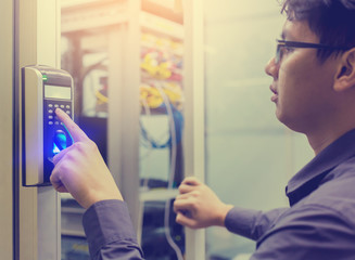 Asian young man press the button of electronic control machine with finger scan to access the door of control room or data center.